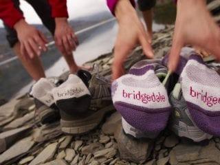 Δύο χέρια πιάνουν κάλτσες πάνω σε παπούτσια διπλά σε λίμνη